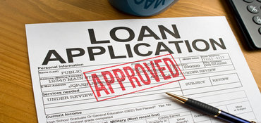Loan Application with Approved rubber stamped on a desktop.
